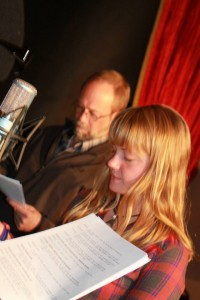 Erika Kooda, associate producer and voice actress, performs during a sketch in the Dec. 14, 2013 Great Northern Radio Show in Fosston, Minnesota, while actor Mark Christensen prepares to jump in. PHOTO: Shelly Hanson