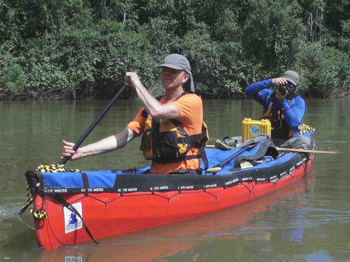 "Paul Schurke paddles while Dave Freeman takes a picture during their expedition along the Rio Roosevent (""River of Doubt"") in Brazil."