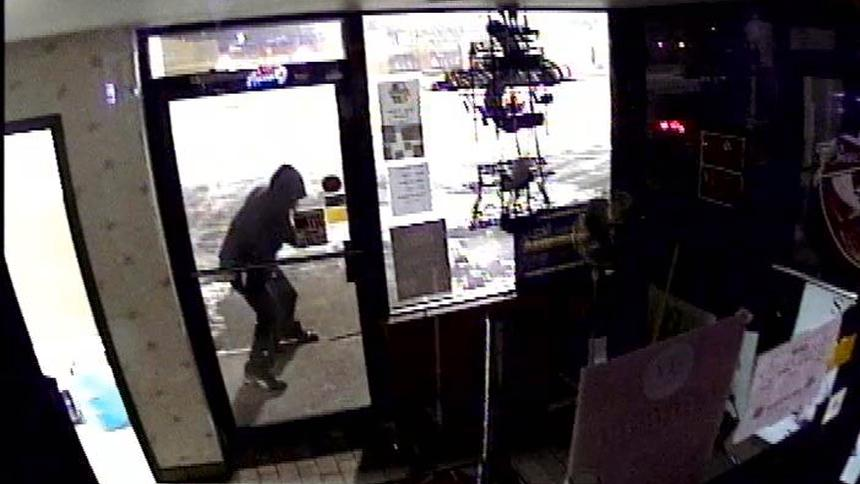 "A suspect prepares to break the door of the ""Some Beach"" liquor store in Hibbing, where he absconded with three cases of Keystone Light. (PHOTO via Hibbing Police Department)."