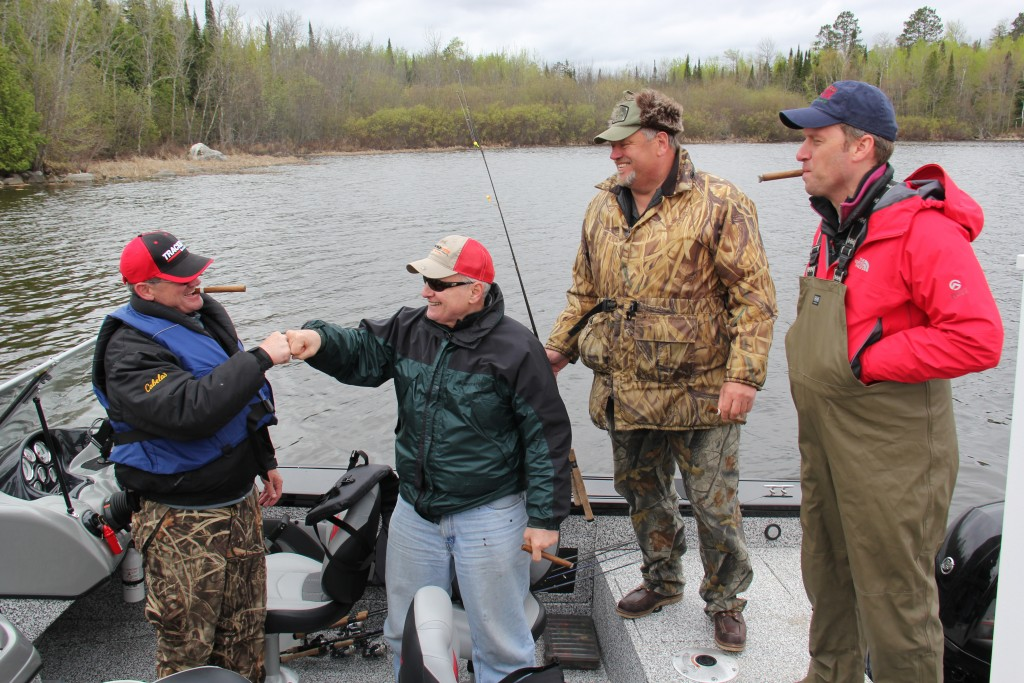 Governor Dayton thanks his fishing guide, Buck Lescarbeau, with a fist bump after a successful fishing expedition. Senate Majority Leader Tom Bakk and House Speaker Kurt Daudt look on. (PHOTO: Office of the Governor)