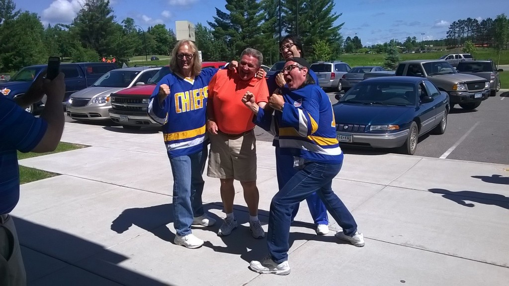 """Real-life brothers and former pro hockey players Jeff, Steve and Jack Carlson, who portrayed the iconic """"Hanson Brothers"""" in the Paul Newman film """"Slap Shot,"""" are seen here """"roughing up"""" Grand Rapids, MN, mayor Dale """"Spud"""" Adams. (PHOTO: via Facebook)"""