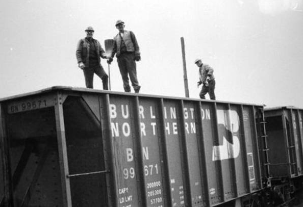 Three laborers stand atop the last shipment of iron ore from Butler Taconite, which closed 30 years ago. By old tradition, workers place a broom in the final shipment of ore from a mine. A tree is placed in the first load of ore from a new mine. (Iron Range Research Center archives).