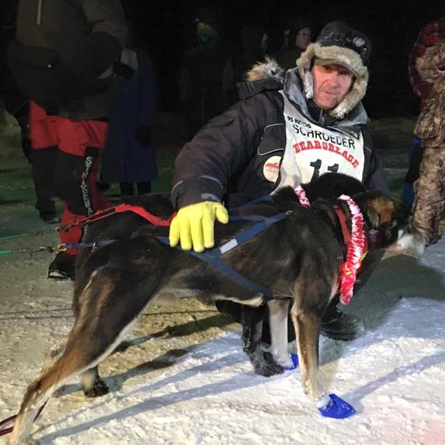 Nathan Schroeder congratulates one of his dogs shortly after winning the 2016 Beargrease Sled Dog Marathon. (PHOTO by Alli Gerths via Beargrease social media)