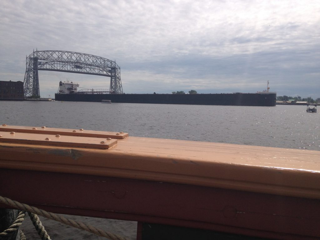 The ore freighter American Integrity passes under the Aerial Lift Bridge, as seen from the deck of the replica pirate-hunting ship the USS Niagara. (Aaron J. Brown)