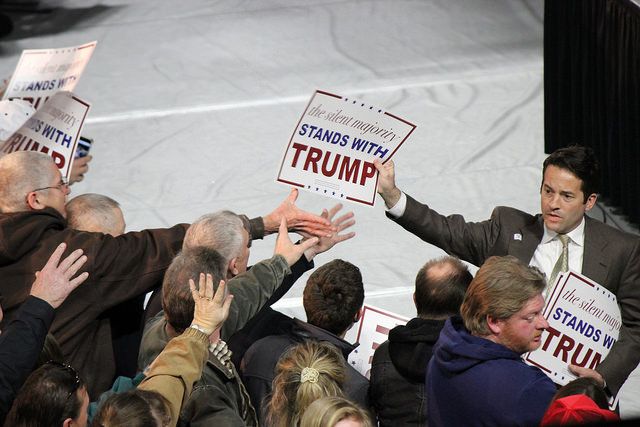 People reach for signs at a Donald Trump rally in January 2016. (PHOTO: Evan Guest, Flickr CC)